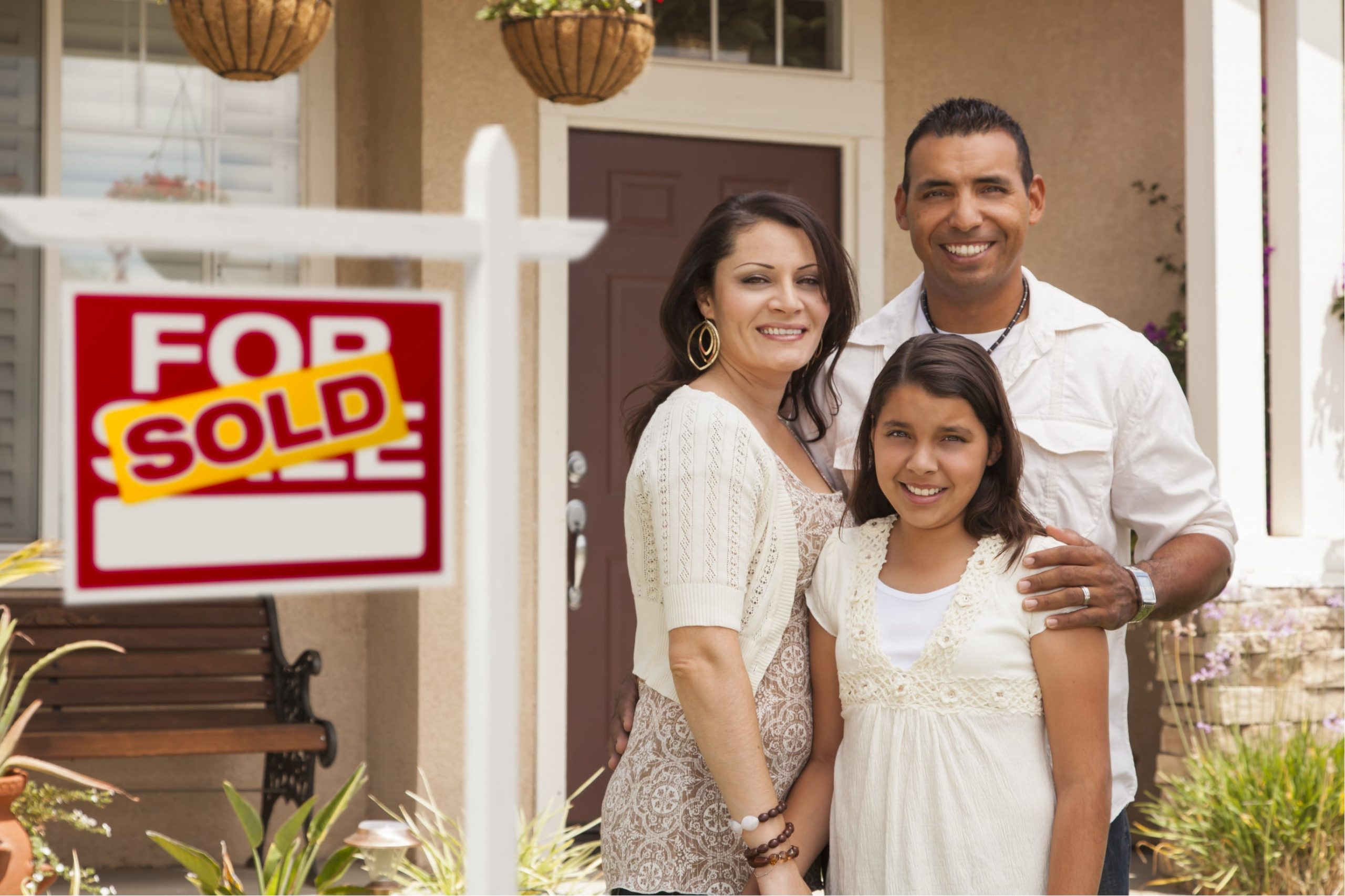 """Happy Family Standing in front of a house that has a """"sold"""" sign after getting a home loan"""