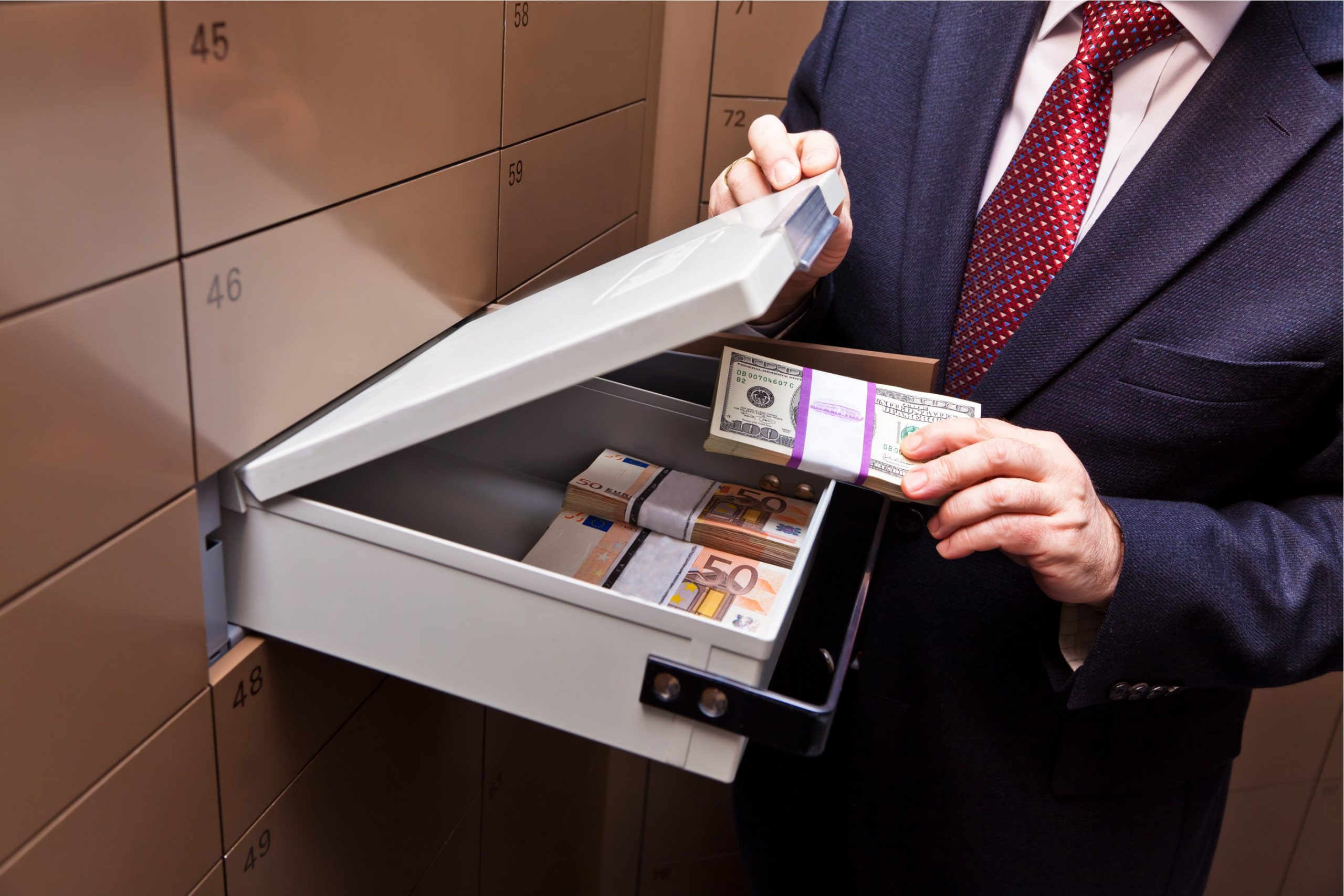 Man putting money into a safe deposit box as he's getting a home loan